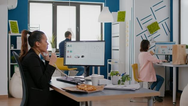 Multitasking-manager bespricht marketingstrategie mit remote-mitarbeitern über festnetz, während er während der mittagspause eine lieferpizza isst