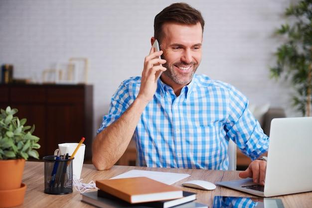 Multitasking-mann, der in seinem büro arbeitet