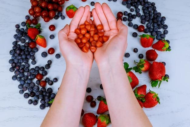 Multivitaminergänzungen von der frucht auf weißem hölzernem hintergrund