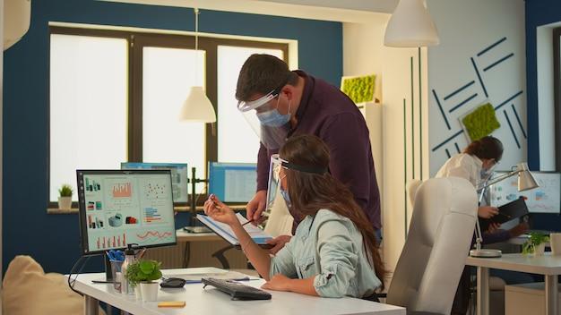 Multy-ethnische gruppe junger geschäftsleute, die in einem neuen normalen büroraum sitzen und mit einem computer arbeiten, der eine schutzmaske und ein visier trägt und die soziale distanz respektiert. teamplanung finanzstrategie