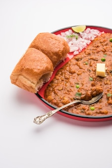 Mumbai style pav bhaji ist ein fastfood-gericht aus indien, besteht aus einem dicken gemüsecurry, serviert mit einem weichen brötchen, serviert auf einem teller