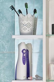 Munddusche oder wasserflosser mit austauschbarer düse und zahnbürsten unter den toilettenartikeln auf dem wandschrankregal im badezimmer.