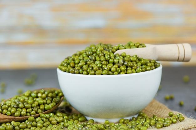 Mungobohnen auf schüssellandwirtschaftsprodukten auf dem sack - trocknen sie grüne mungobohnen