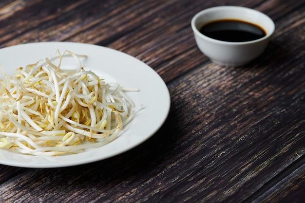 Mungobohnensprossen in der platte. rohes organisches gesundes lebensmittel. traditioneller gemüseteller in ostasien.