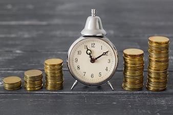 Münzen und ein Wecker - rechtzeitige Zahlung einer Schuld unter dem Kredit.