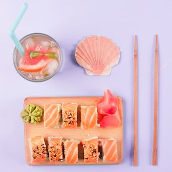 Muschel mit muscheln; grapefruitsaft; essstäbchen; lachssushi mit wasabi und eingelegtem ingwer auf schneidebrett vor violettem hintergrund