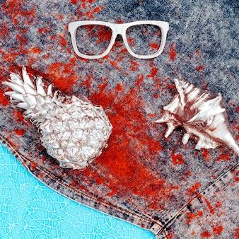 Muschelananasgläser auf einem jeanshintergrund. minimale kunst
