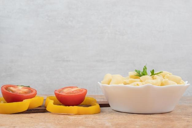 Muschelförmige nudeln in schüssel mit paprika- und tomatenscheiben.