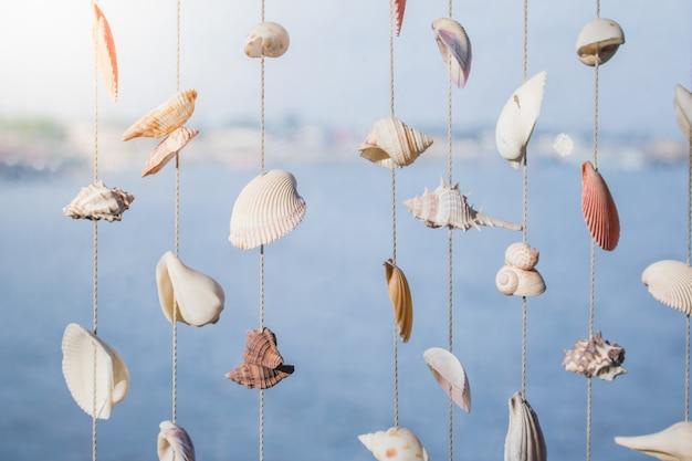 Muscheln, die an den schnüren für dekoration hängen