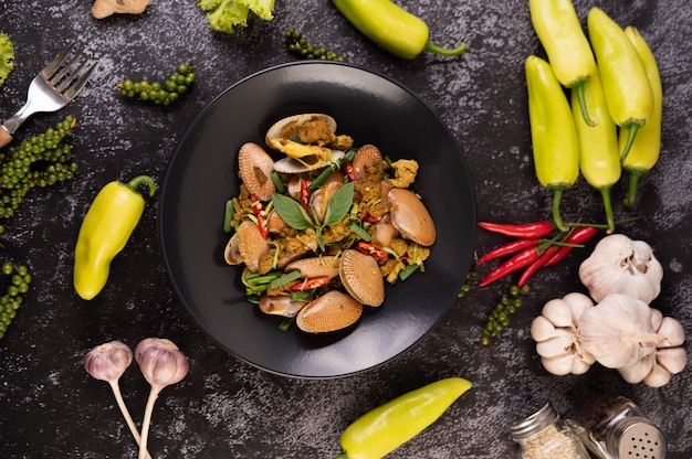 Muscheln gebratenes currypulver auf einem schwarzen teller.
