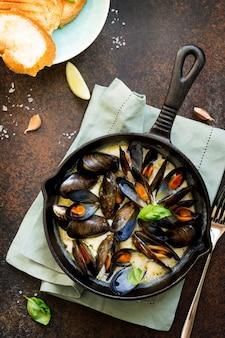 Muscheln gekocht in einer sauce aus weißwein, serviert mit toast und zitrone gourmet italienische küche flat lay draufsicht