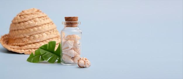 Muscheln in einer mini-flasche, tropische blätter, strohhut. das konzept des meeres, urlaub, reisen