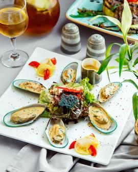 Muscheln in sahnesauce serviert mit grünem salat