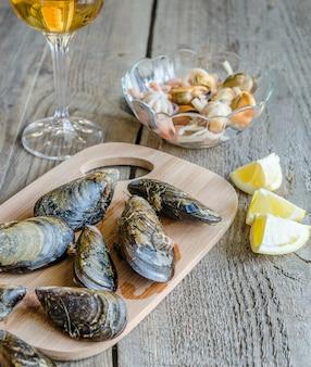 Muscheln mit einem glas weißwein auf dem holztisch
