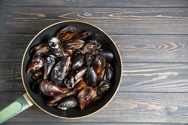 Muscheln mit petersilie und knoblauch in wogpfanne auf holztisch