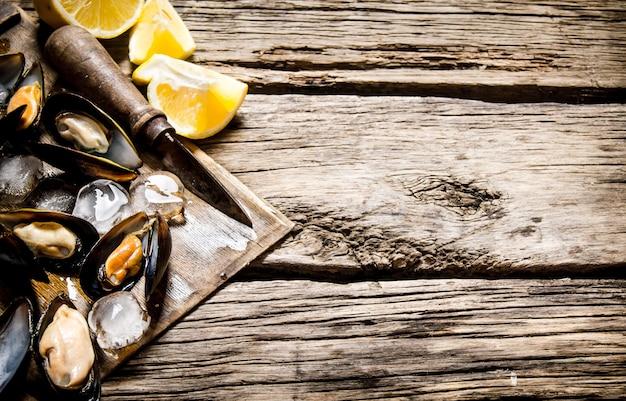 Muscheln mit zitrone und eis auf einem holzbrett. auf hölzernem hintergrund. freier platz für text.