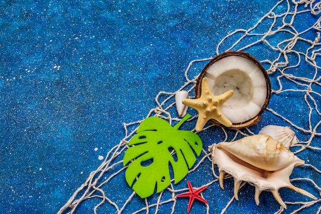 Muscheln, netz, kokosnuss, seesterne und monsterblatt auf blauem glitzer