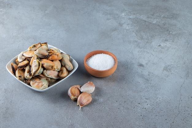 Muscheln ohne schale in einer schüssel auf dem marmorhintergrund.