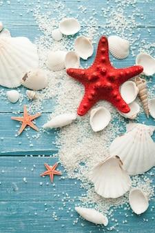 Muscheln, sand und sterne auf einer blauen holzoberfläche
