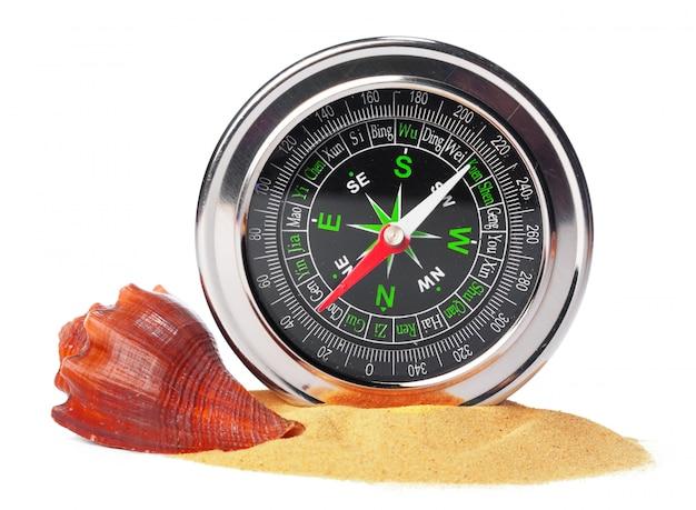 Muscheln und alten kompass mit sand, isoliert auf weiss