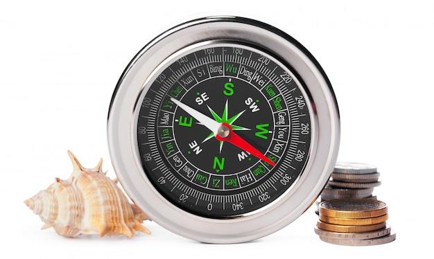 Muscheln und alter kompass mit dem sand lokalisiert auf weiß