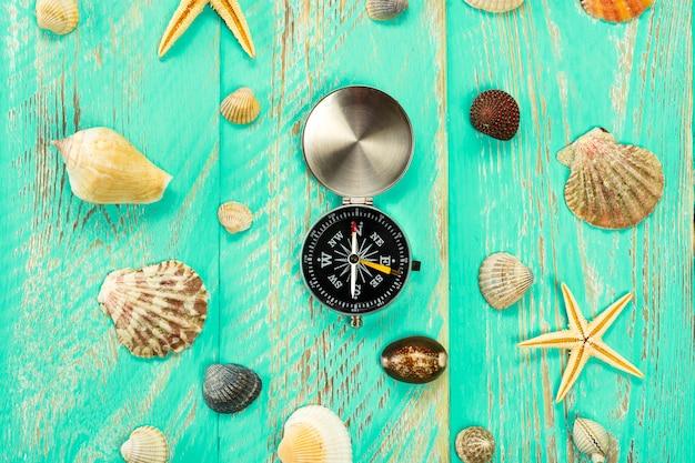 Muscheln und kompass auf blauem holztischhintergrund
