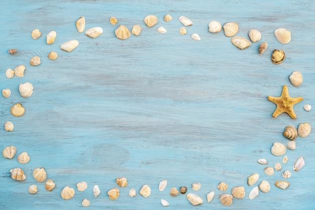 Muschelrahmen auf blauem holz für sommerferienzeithintergrund.
