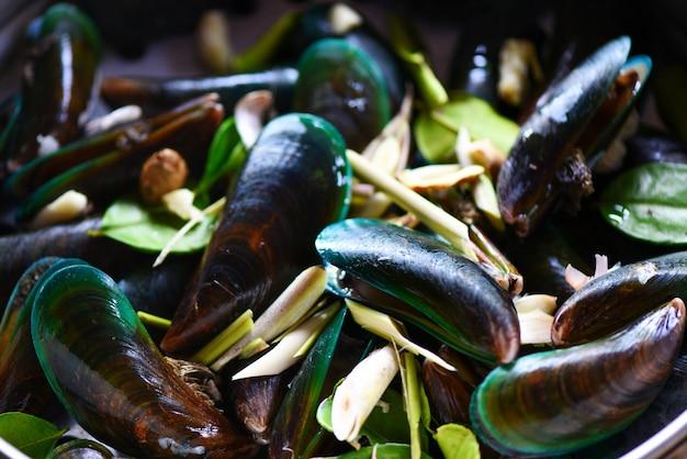 Muschelschale mit kräutern und gewürzen kochte dampfende meeresfrüchte der grünen miesmuschel