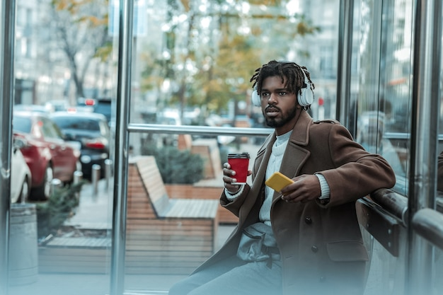 Musik app. aufmerksamer mann, der nach vorne schaut, während auf bus wartet