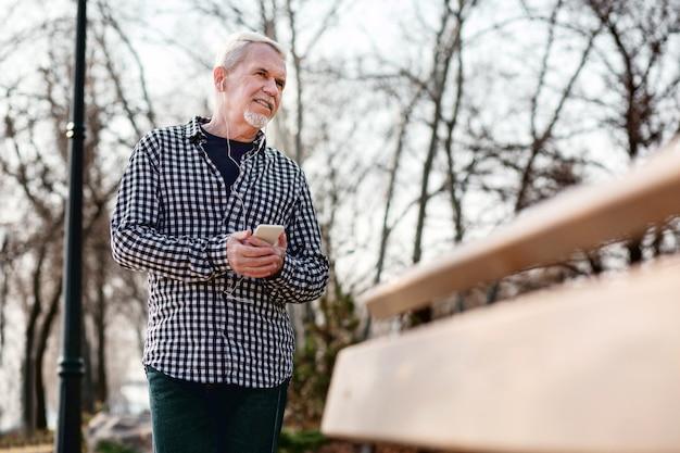 Musik für alle. niedriger winkel des zweifelhaften älteren mannes, der im park steht und musik hört