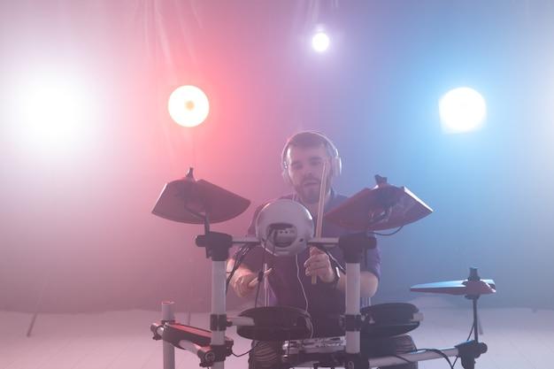 Musik-, hobby- und personenkonzept - junger schlagzeuger, der auf der bühne elektronisches schlagzeug spielt