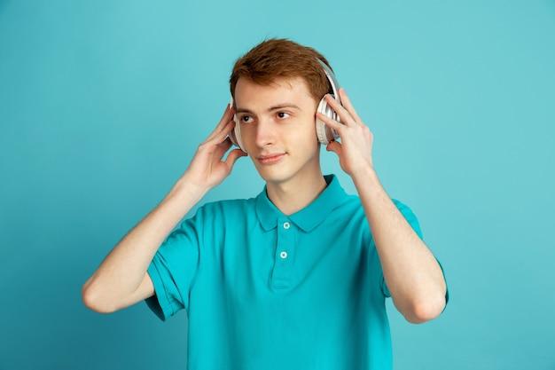 Musik hören. das moderne porträt des kaukasischen jungen mannes lokalisiert auf blauer wand, monochrom. schönes männliches model. konzept der menschlichen emotionen, gesichtsausdruck, verkauf, anzeige, trendy.