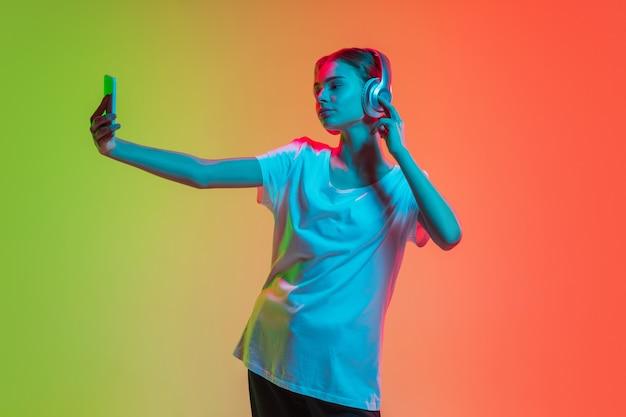 Musik hören mit kopfhörern unter selfie junges kaukasisches mädchenporträt auf farbverlauf