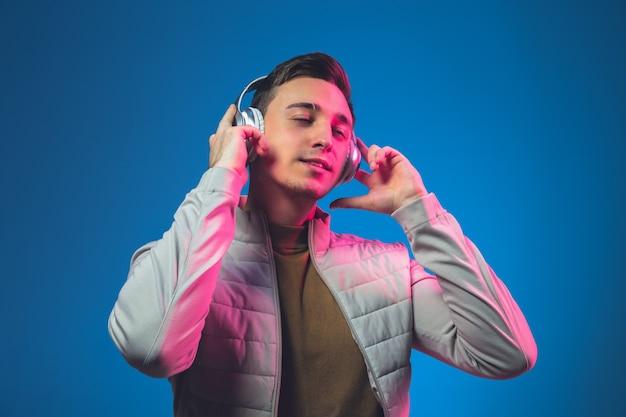 Musik hören. porträt des kaukasischen mannes isoliert auf blauer wand in rosa neonlicht.