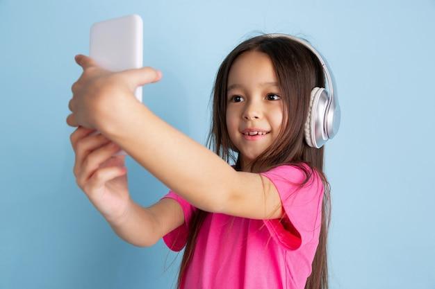 Musik hören, selfie machen. kaukasisches porträt des kleinen mädchens auf blauer wand.