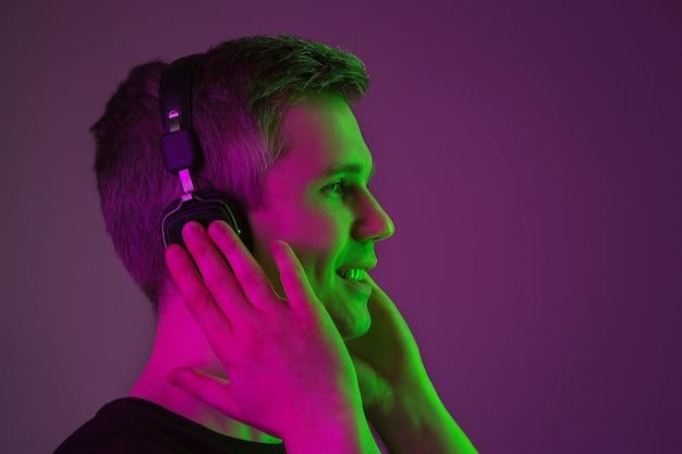 Musik hören, singen, genießen. porträt des kaukasischen mannes auf purpurrotem studiohintergrund im neonlicht. schönes männliches modell im schwarzen hemd. konzept der menschlichen emotionen, gesichtsausdruck, verkauf, anzeige.