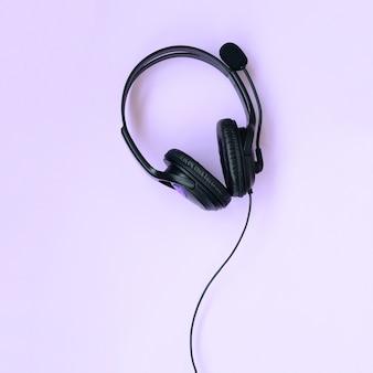 Musik hörendes konzept. schwarze kopfhörer liegen auf violettem hintergrund