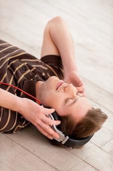 Musik ich mein leben. draufsicht auf einen gutaussehenden jungen mann mit kopfhörern, der die musik hört und die augen geschlossen hält, während er auf dem boden liegt