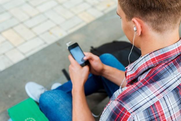 Musik im freien genießen. draufsicht eines jungen mannes, der mp3-player hört, während er an der außentreppe sitzt