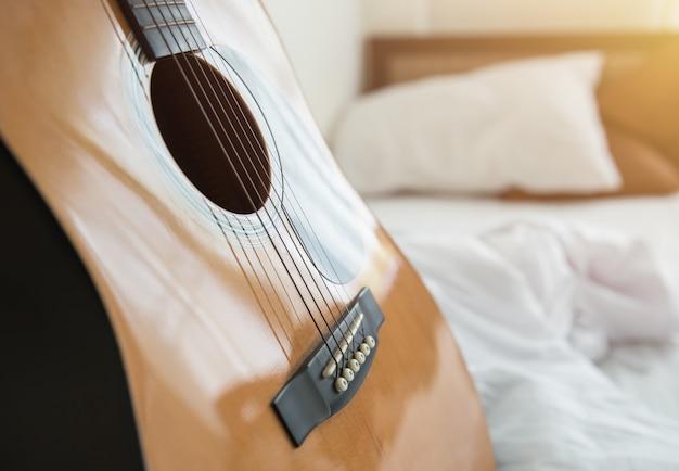 Musik in der schlafzimmermorgen-konzeptgitarre mit weißem bett
