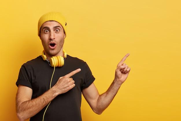 Musik ist teil der technologie. der überraschte kaukasische mann trägt kopfhörer, gelbe kopfbedeckungen und ein schwarzes t-shirt