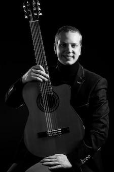 Musik. junger musiker im schwarzen anzug, der eine gitarre hält