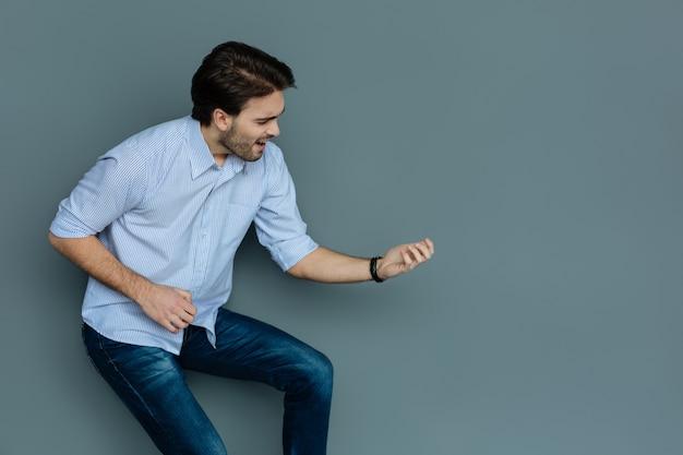 Musik komponist. fröhlicher positiver netter mann, der ein musikinstrument hält und es spielt, während er in den prozess involviert ist