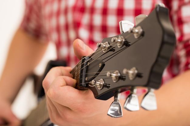 Musik, nahaufnahme. musiker, der eine hölzerne gitarre anhält Kostenlose Fotos