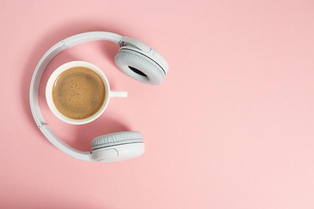 Musik- oder podcast-konzept mit kopfhörern und tasse kaffee auf rosa tisch, flach liegen. draufsicht, flach liegen