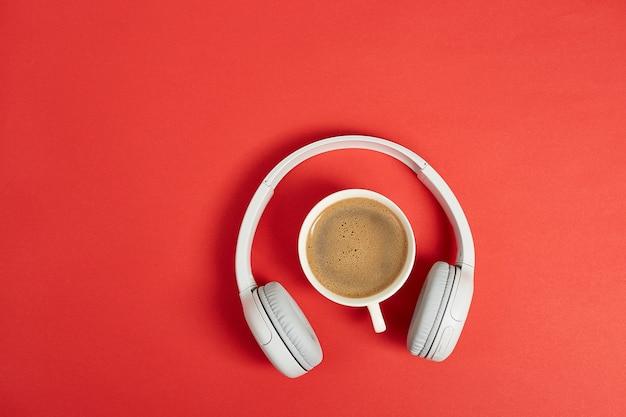 Musik- oder podcast-konzept mit kopfhörern und tasse kaffee. draufsicht, flach liegen
