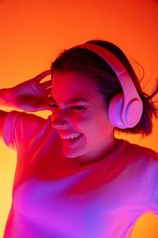 Musik. porträt der kaukasischen frau auf rosa studiohintergrund im trendigen neonlicht. schönes weibliches modell mit kopfhörern. konzept der menschlichen emotionen, gesichtsausdruck, verkauf, werbung, mode.