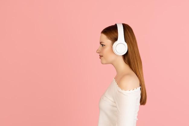 Musik. porträt der kaukasischen frau auf rosa wand mit exemplar für anzeige isoliert. schöne frau mit kopfhörern. konzept der menschlichen emotionen, gesichtsausdruck, jugendkultur.