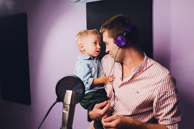 Musik-, showbusiness-, people- und voice-konzept - sänger mit kopfhörern und mikrofon im tonstudio.