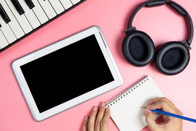 Musik-songschreiber schreibt auf ein notizbuch mit leerem tablettenschirm für musikanwendungsspott oben